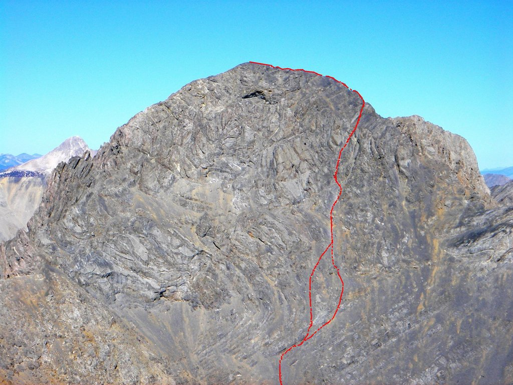 This photo of the south face by Judi Steciak accurately shows the Southeast Face route pioneered by Rick Baugher in 1990. The photo was taken from Big Boy Peak. Please note that when you are at the base of the face, the perspective is much different and it takes a bit of study and experience to find the route through the confusing face from below.