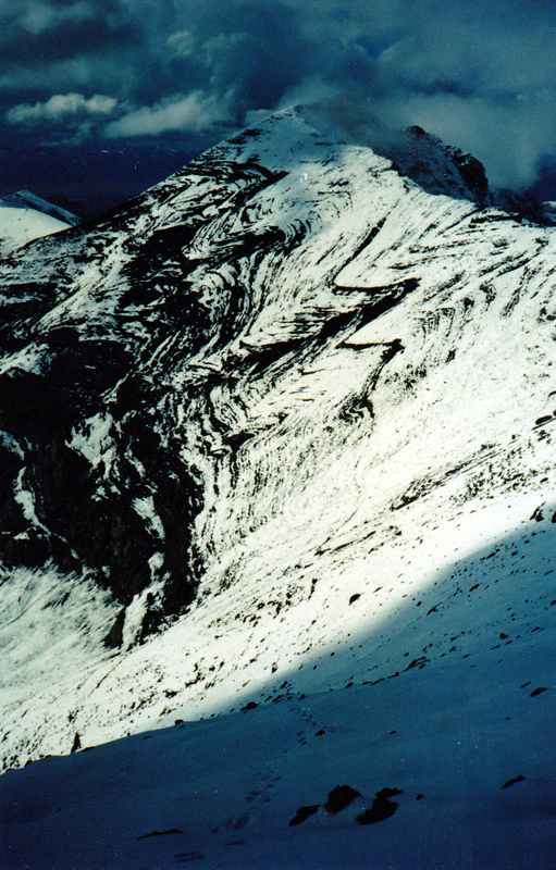 Note the contorted limestone chevron folds on the south east facer of Huhs Horn. This photo was taken while descending down the headwall of Scott Peak. Rick Baugher Photo and Commentary.