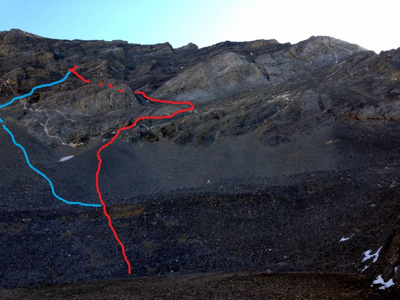 There are two lines that lead up the lower half of the headwall from the pond. The original line is shown in blue. It climbs a steep talus pile and then follows a rubble covered shelf to up and to the right. The line shown in red follows steeper and more exposed ledges. Both routes meet above the first series of cliffs about half way up the face.