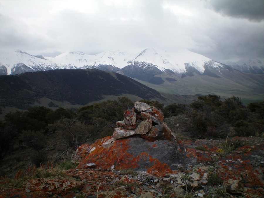 The summit cairn atop Peak 8256 with the snow-laden Pahsimeroi Range in the background on a stormy afternoon in May. Livingston Douglas Photo