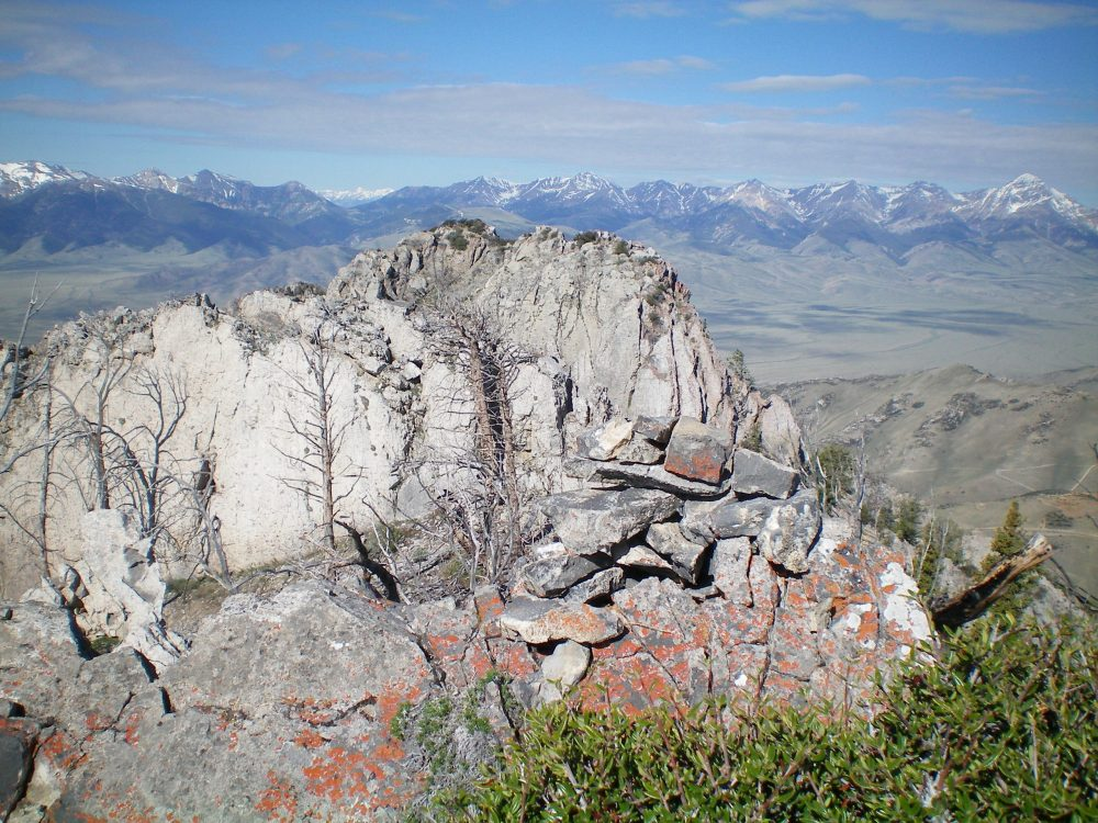 The summit cairn atop Peak 9085 with the ridge towers to the Southwest just behind it. The Lemhi Range is in the distance. Livingston Douglas Photo