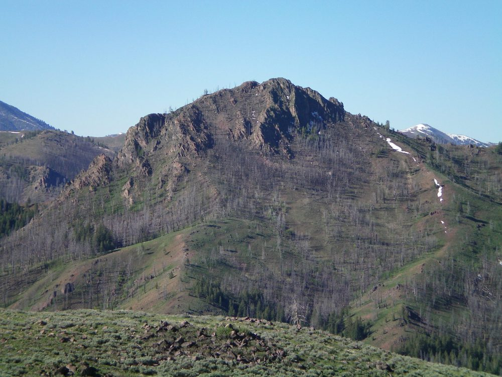 The North Side of rugged Mahoney Butte. The North Couloir is visible in dead-center, with small snow patches in it. The summit is the highest hump just right of center. Livingston Douglas Photo