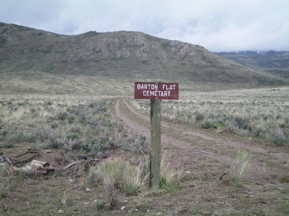 "Sign for ""Barton Cemetary"" (mis-spelled) at the 4-way road junction. The easy, lower section of the North Ridge of Lehman Butte is in the background. Livingston Douglas Photo"