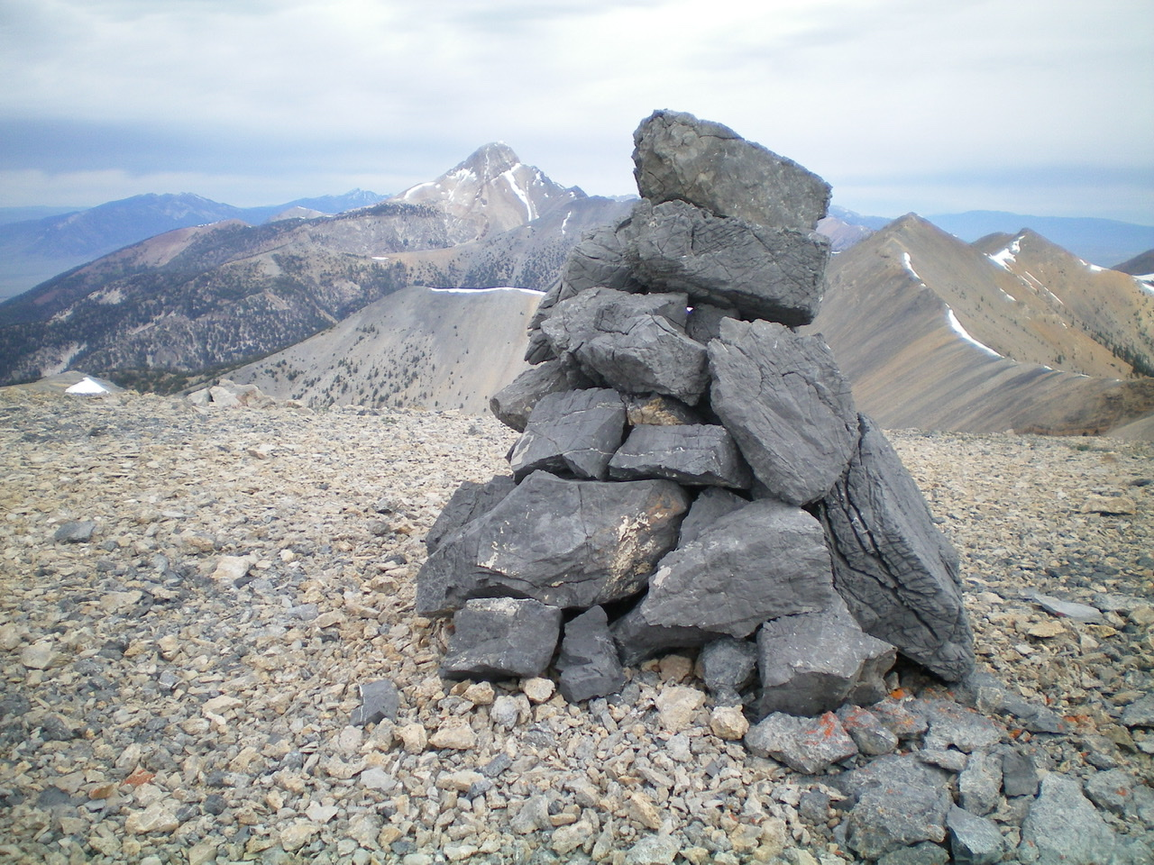 The black-rock summit cairn atop Midway Mountain, with Bell Mountain in the background. Livingston Douglas Photo