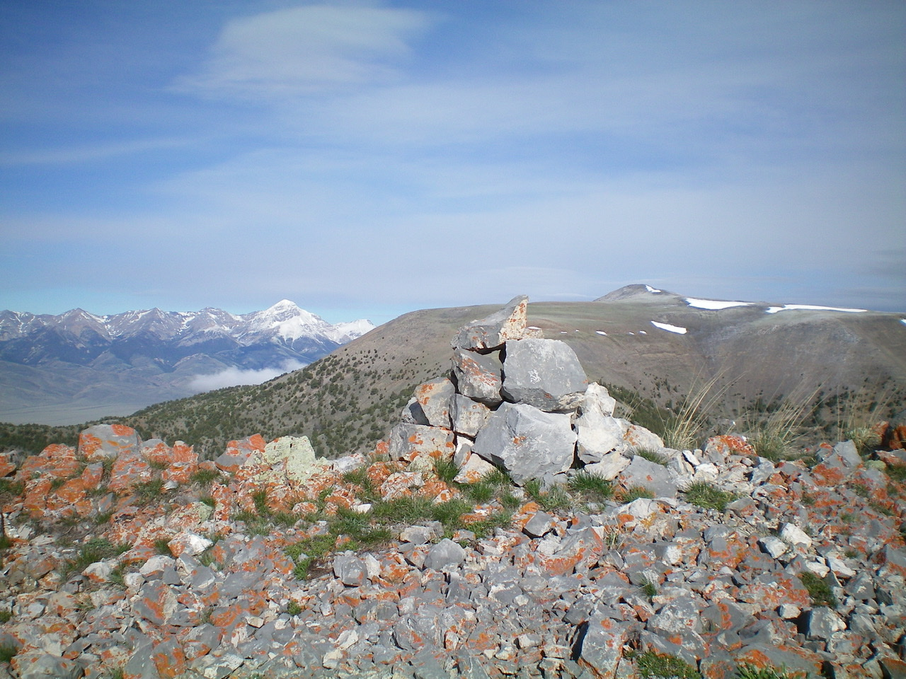 The summit cairn atop Peak 9877 with Copper Mountain (right of center) and snow-clad Diamond Peak (left of center) in the distance. Livingston Douglas Photo