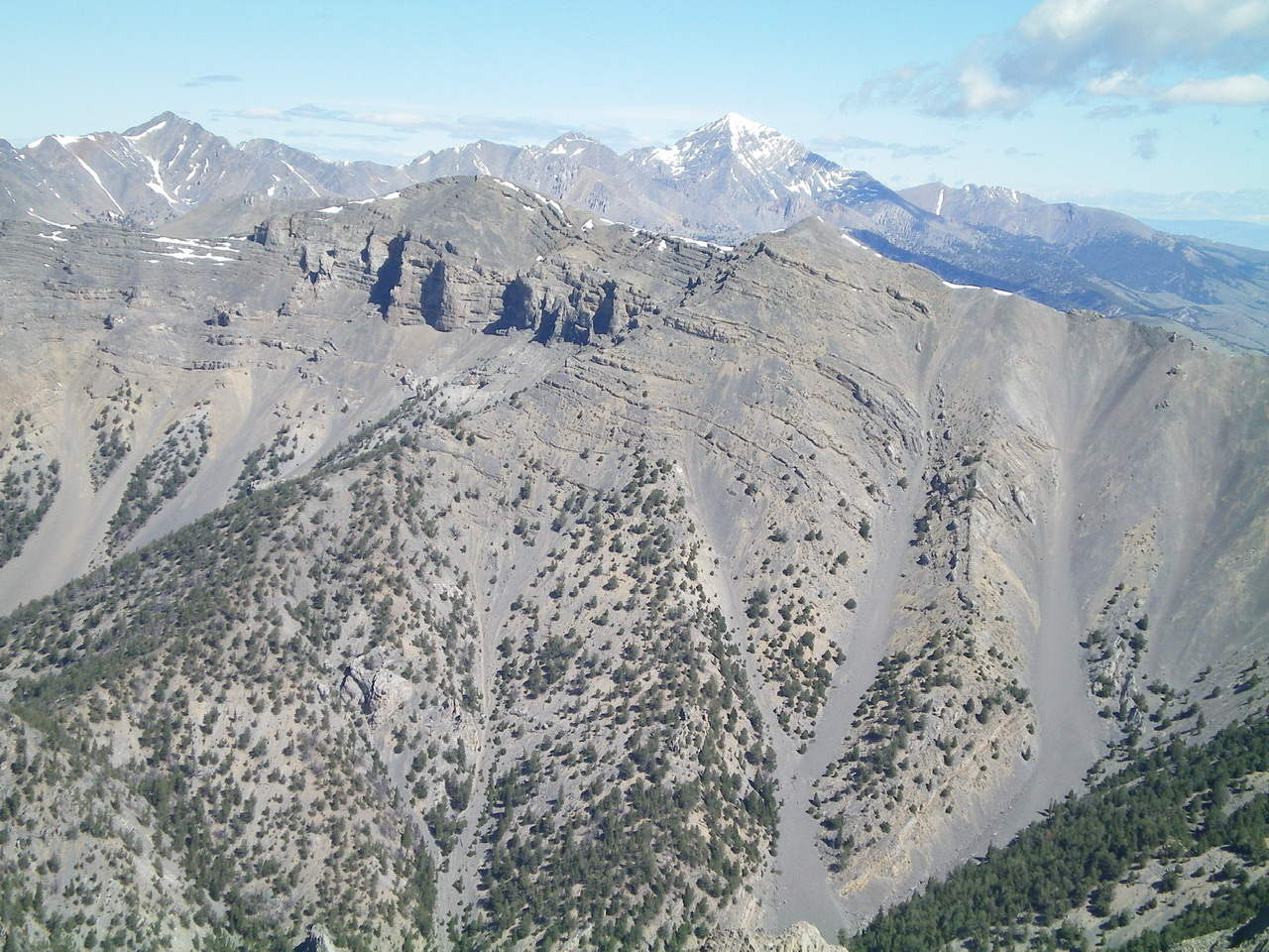 Shril Benchmark (left of center) and Point 10601 (right of center) and the magnificent South Ridge (descending diagonally leftward) with snow-capped Diamond Peak in the distance. Livingston Douglas Photo