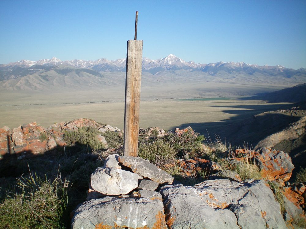 The summit cairn atop Peak 7413 with Diamond Peak in the background, just right of the summit post. Livingston Douglas Photo