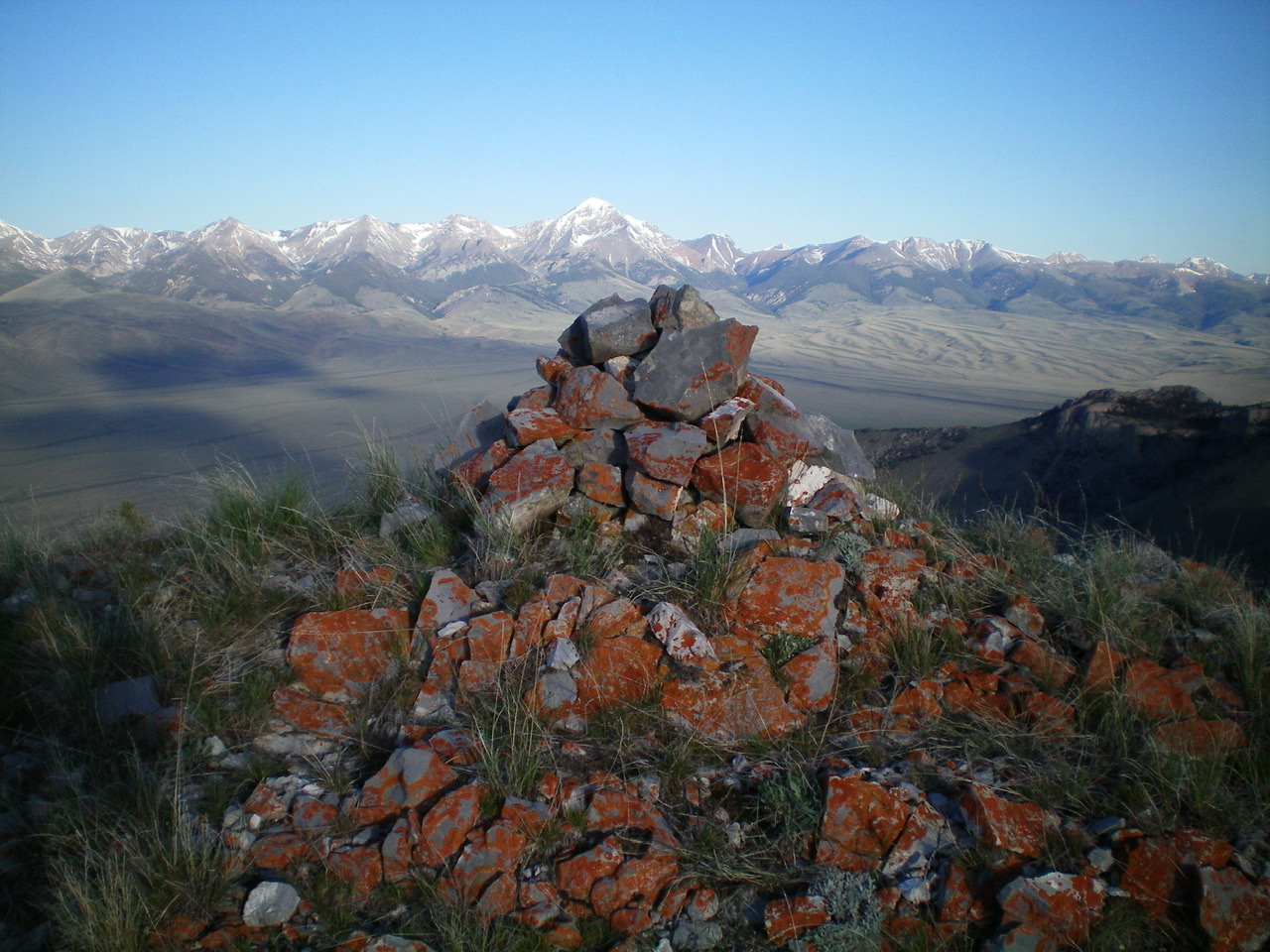 The summit cairn atop Peak 7910 with snow-capped Diamond Peak in the distance. Livingston Douglas Photo