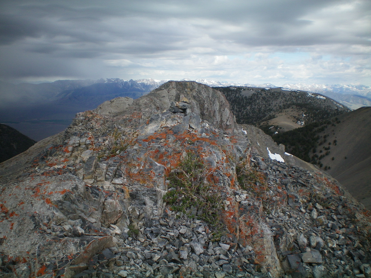 The rocky summit of Dome Peak with its small summit cairn. The false summit is the rocky outcrop in the background. A thunderstorm is rolling in. Livingston Douglas Photo