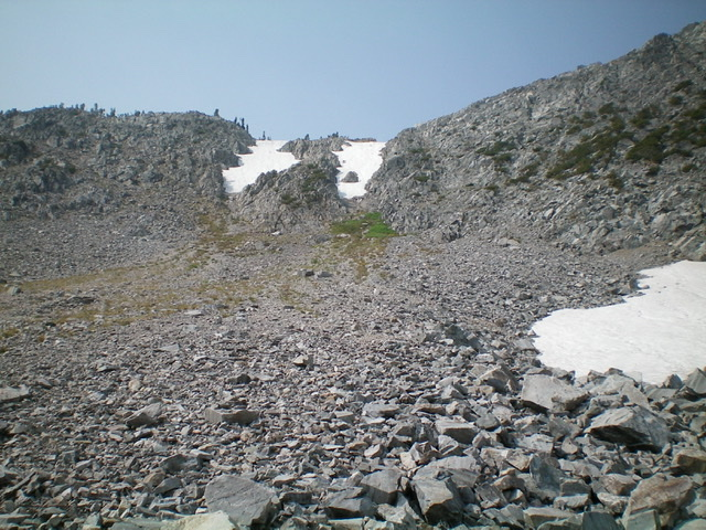 Looking up at the Ajax Peak/Don Moore Peak saddle from a talus basin high above Ajax Lake. Note the permanent snowfields in two couloirs on the east side of the saddle AND the snowfield on the right side of the picture. The direct route goes up the Class 3 arete on the left side of the leftmost, snow-filled couloir. The trail route goes up a diagonal trail that starts just left of the nearby snowfield (in the talus basin) and goes left/southwest up to the ridgeline well south of the saddle. A ridge scramble north down to the saddle is required after reaching the ridge via the trail. When ascending from Ajax Lake, look for those two high snow-filled couloirs to guide you to the talus basin. Livingston Douglas Photo
