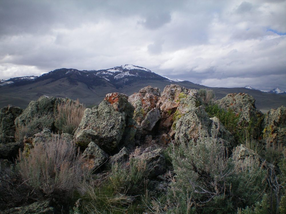 The summit boulders atop Bartlett Point with the snow-capped [higher] Boulder Mountains in the background. Livingston Douglas Photo
