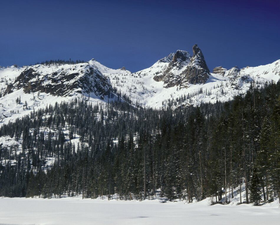 """1. Our first day was spent skiing up Hell Roaring road down in the forest, the end of the road being Camp I. Semi-unplanned as it was we hooked up with a Boise contingent of the DFC&FC* on the ski in, boosting our group to seven adventuresome lads. The second morning we were greeted with scenery. The fickle """"Finger of Fate"""" is seen pointing skyward in this view from the outlet at Hell Roaring lake, flanked by the Arrowhead and the Birthday Cake on the skyline. * Decker Flats Climbing & Frisbee Club"""