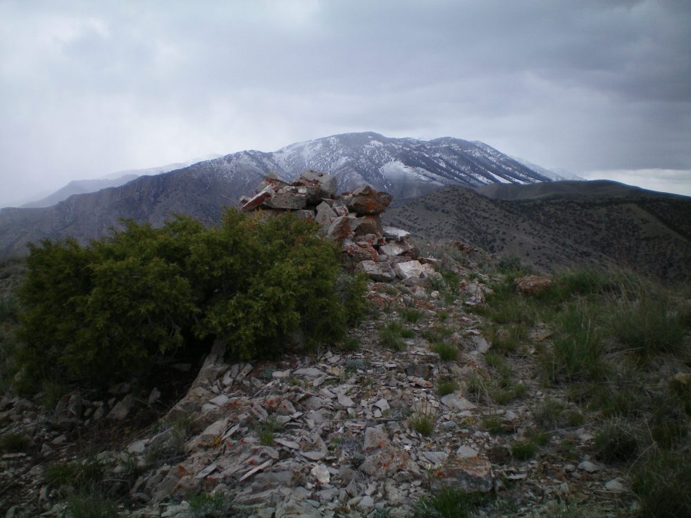 The summit cairn atop peak 6570. The snow-dusted Lemhi Mountains to the north are in the background. It was a cold, blustery May day with scattered snow showers. Livingston Douglas Photo