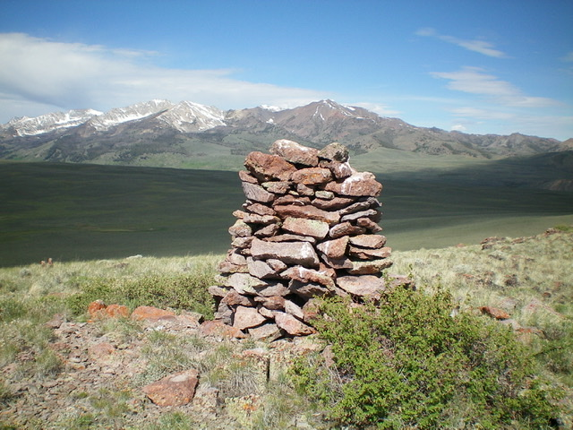 The tall summit cairn atop Reed and Davis Benchmark with the snow-filled east faces of the Pioneer Mountains in the distance. Livingston Douglas Photo