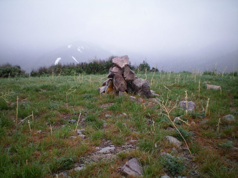 The newly-built summit cairn atop Peak 7058, on a cold, rainy morning in mid-May. Livingston Douglas Photo