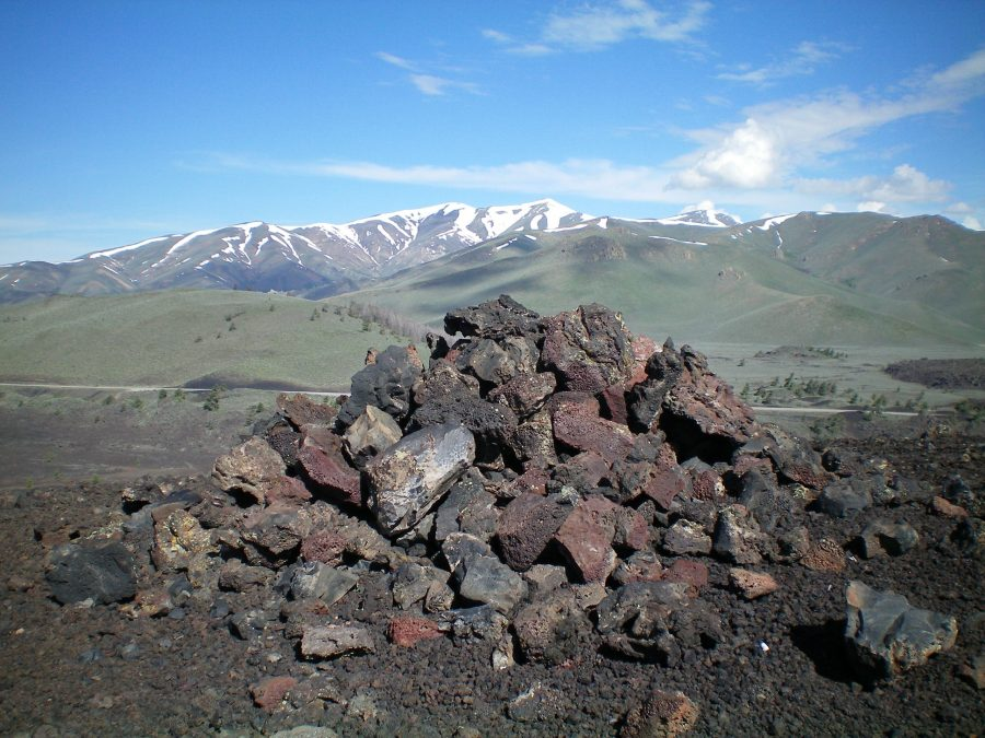 The large summit cairn atop the high point of North Crater. Snow-clad Blizzard Mountain is in the distance. Livingston Douglas Photo