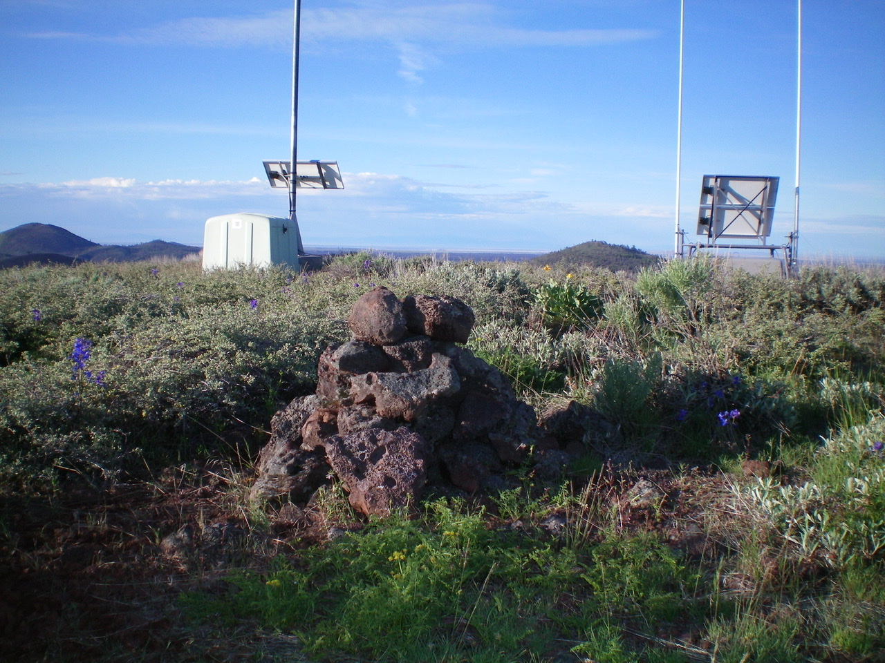 The summit cairn atop Sunset Cone with the 2 repeaters in the background. Livingston Douglas Photo