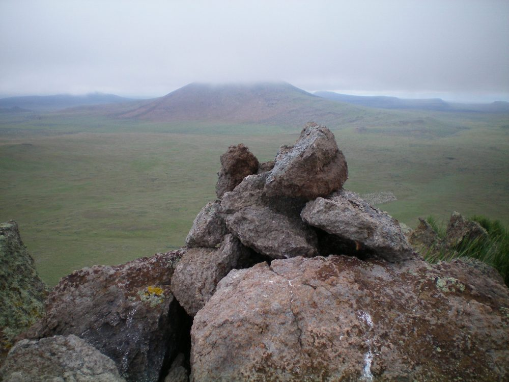 The newly-built summit cairn atop Peak 5273 with cloud-shrouded Wedge Butte in the background. Notice the herd of sheep down on the valley floor (just right of the cairn—look closely). Livingston Douglas Photo