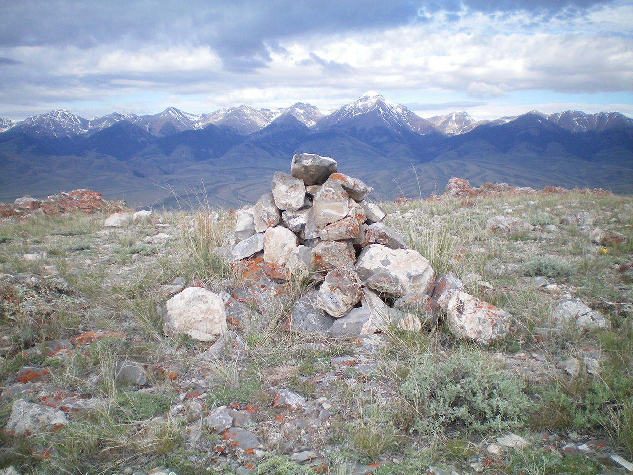 The newly rebuilt summit cairn atop Peak 7830. Diamond Peak is in the distance, just right of center. Livingston Douglas Photo