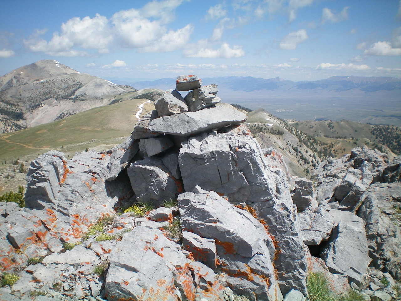 The summit cairn atop the N end of the summit plateau of Big Windy Peak, looking north. Sheep Mountain is left of center in the distance. Livingston Douglas Photo