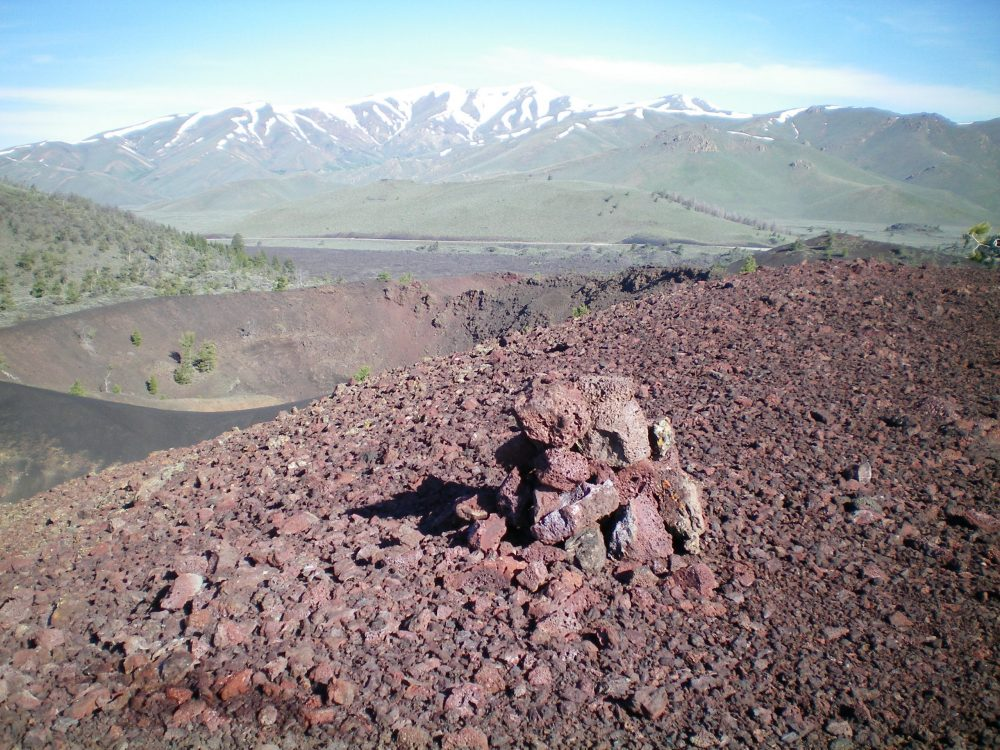 "The summit cairn atop Big Craters on the high point of the crumbly, red lava rock on the East Rim. You can see the Center Crater up and to the left of the cairn. Notice the dark-colored gravel ""ridge"" in front of the Center Crater; it separates the Center Crater from the Southeast Crater. That narrow ridge is the ""cat walk"" in the Northwest Ridge descent route. Snow-clad Blizzard Mountain is in the distance. Livingston Douglas Photo"