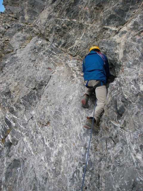Carl Hamke placing protection in the crack above the whitish wall.