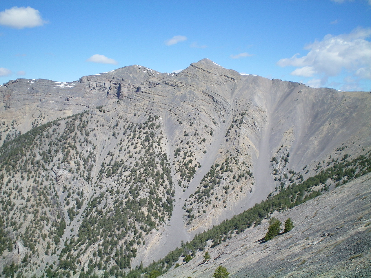 Point 10601 (slightly right of center), the South Ridge (descending leftward), and the crumbly scree/gravel that must be navigated on the Southeast Face to descend the steps/breaks in the ridge. Watch your step up here! Livingston Douglas Photo