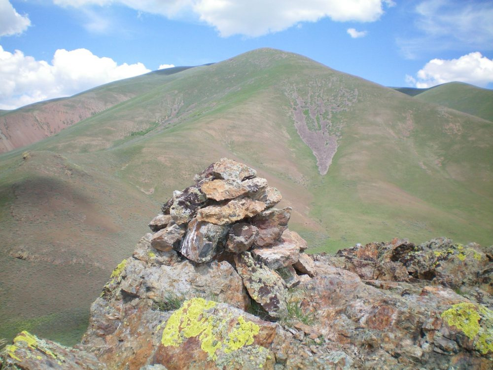 The summit cairn atop Peak 5764 with Peak 7900 in the background. Livingston Douglas Photo