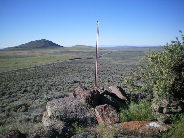The summit cairn and summit post atop Magic Benchmark. Wedge Butte is in the distance, with ID-75 diagonally in between. Livingston Douglas Photo