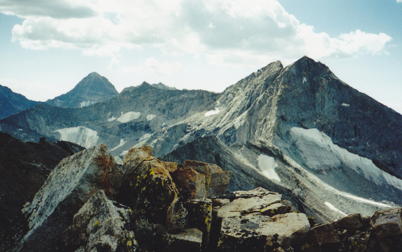 From the pristine summit of Abel Peak, this view is looking south to Goat Moutnain (climber on the summit). The NE ridge of Goat is rated a difficult 5.8 climb. Note the permanent ice features in this section. Hyndman Peak is on the left. Rick Baugher Photo and Commentary 9-17-94