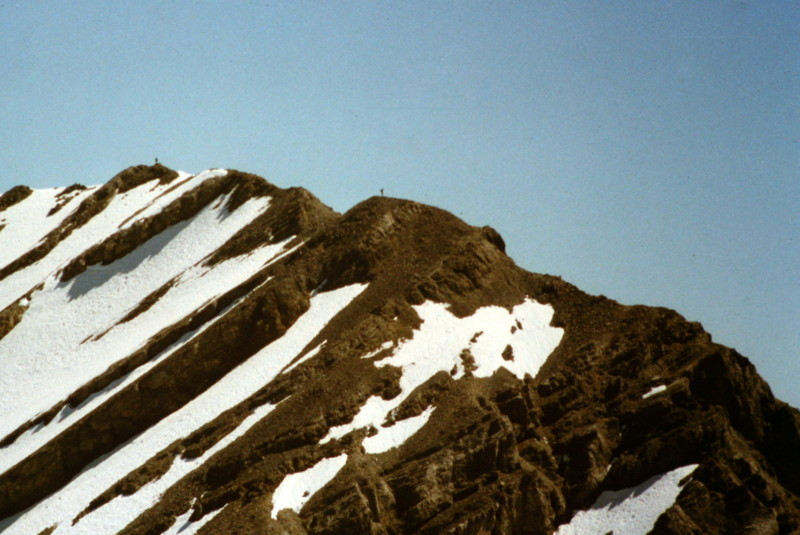 Mount Church viewed from Bad Rock Peak and showing two climbers on the summit ridge.