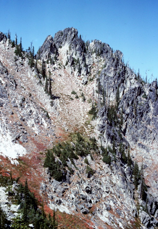 The route up Chimney Peak cuts diagonally up the steep meadow from bottom left to the right side of the photo's high point.