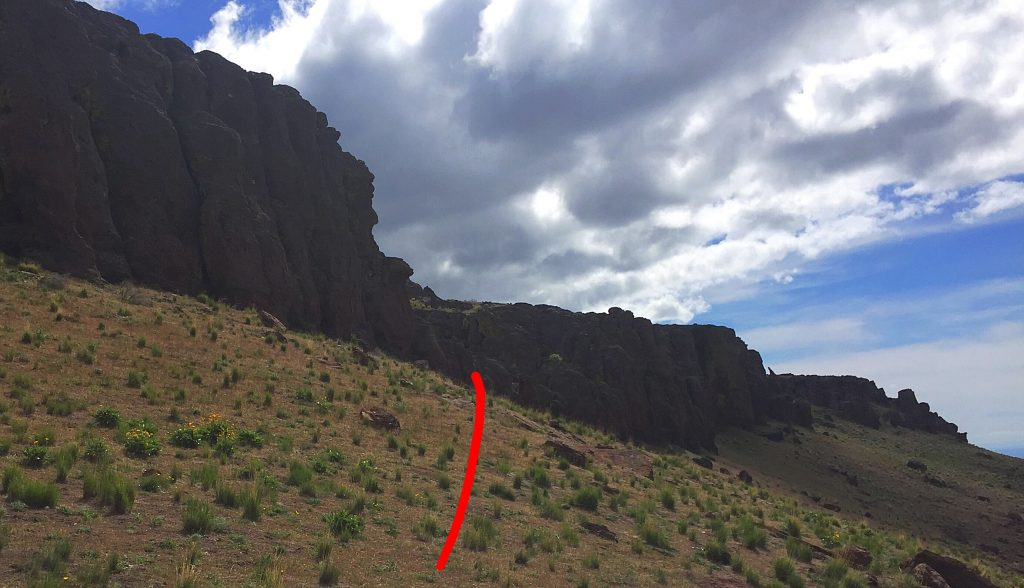 The cliff crown on the south side viewed from the west. The red line leads to the Class 2 opening in the cliffs.
