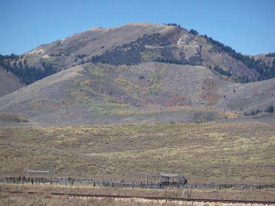 Wooley Range HP. View N from Dry Valley on 9/25/14. Note the mining scars now in restoration on the peak's south slopes. Ascent went up forested draw, far left, to reach the open brush face. Rick Baugher Photo